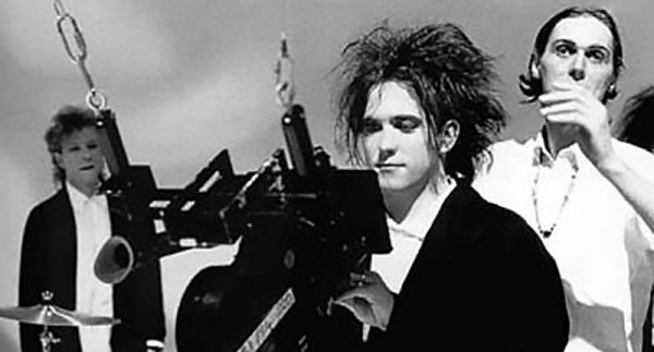 Robert Smith of the Cure looks into the camera as Tim Pope (behind in) prepares the next shot.